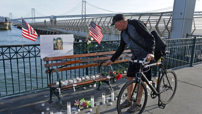 Craig Warner of Palo Alto, Calif., leaves a bell at a memorial site for Kate Steinle on Pier 14 Frid