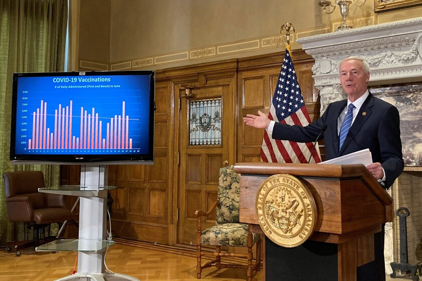 """Asa Hutchinson, behind a lectern that bears the state seal, gestures to a screen labeled """"COVID-19 vaccinations."""""""