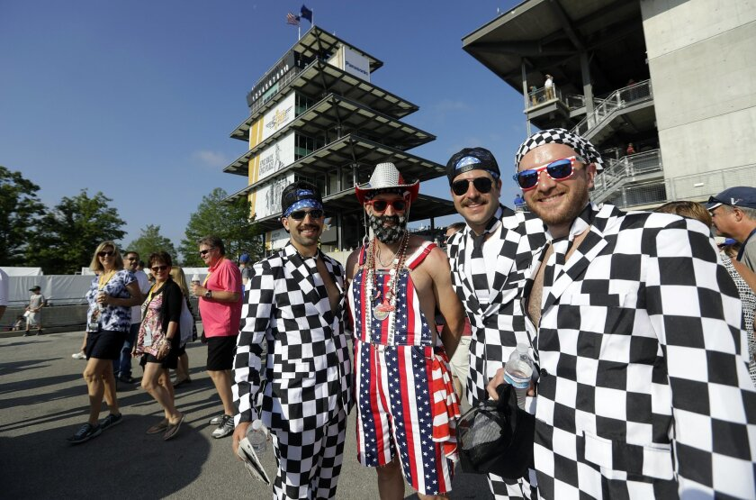 Fans dressed in checked flags and patriotic gear pose for a photo before the 100th running of the Indianapolis 500 auto race at Indianapolis Motor Speedway in Indianapolis, Sunday, May 29, 2016. (AP Photo/Darron Cummings)