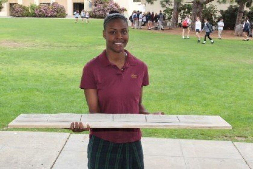 Bishop's School senior Imani Littleton carries tiles from the ceramics room.