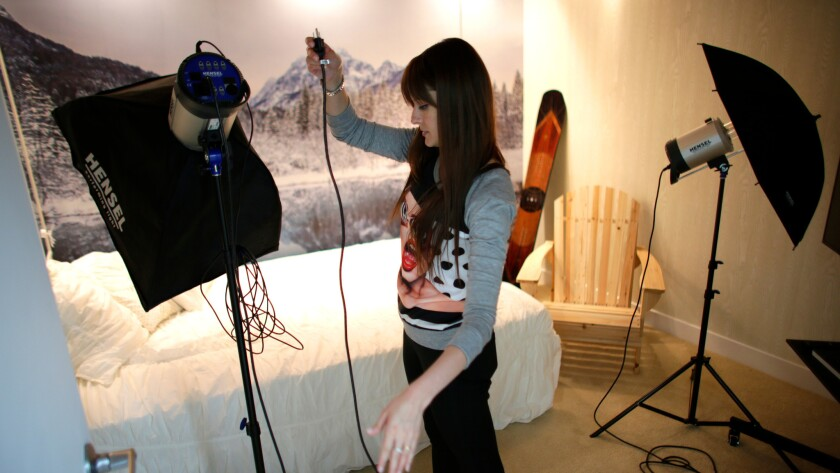 Photographer Anna Krivenkoff sets up lights for a photo shoot at Studio 20.