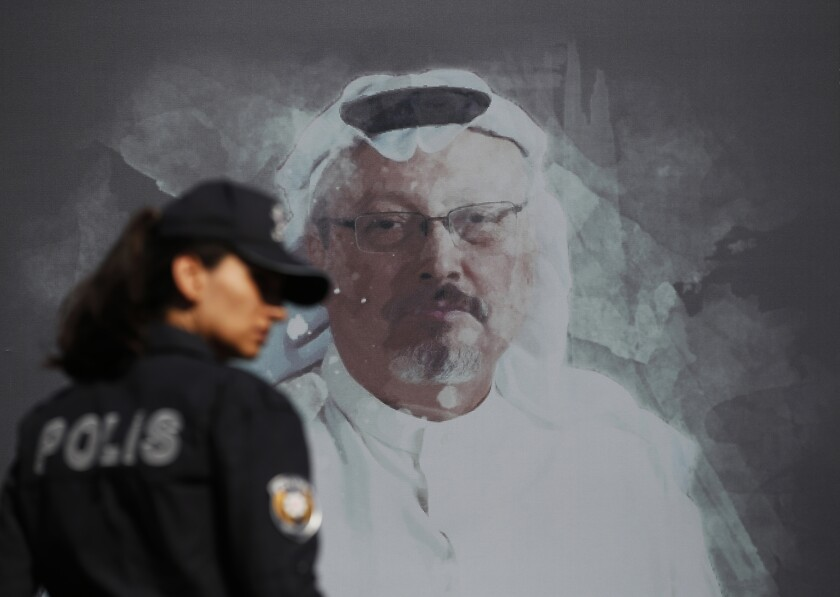 A Turkish police officer walks past a picture of slain Saudi journalist Jamal Khashoggi prior to a ceremony marking the one-year anniversary of his death