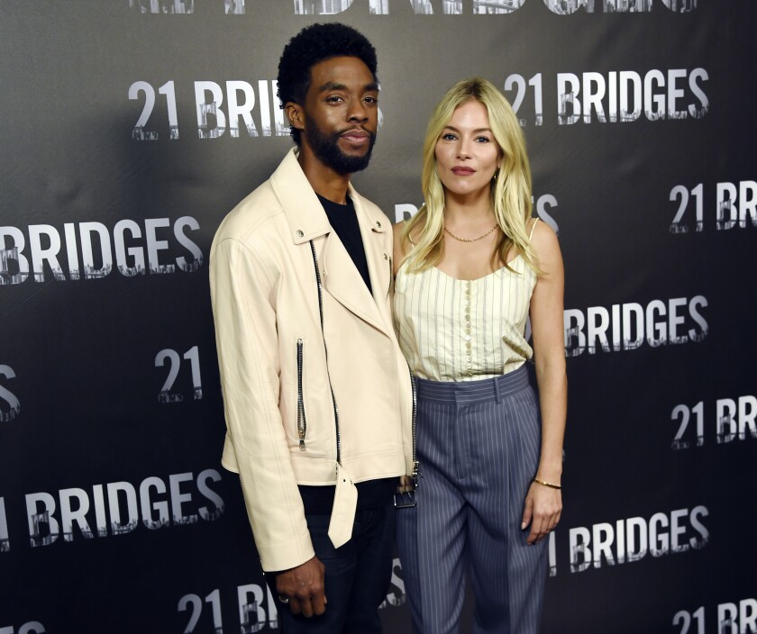 "Actors Chadwick Boseman and Sienna Miller appear together at an event for the 2019 film, ""21 Bridges."""