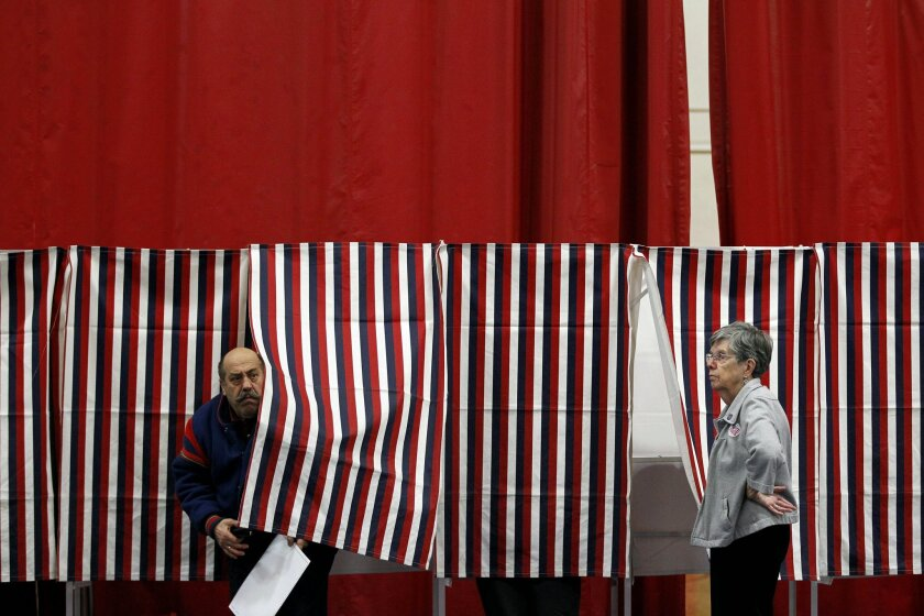 FILE - In this Jan. 10, 2012, file photo, ballot inspector Connie Bell, right, holds open a curtain on a voting booth during voting in the first-in-the-nation presidential primary at Memorial High School in Manchester, N.H. It's been 100 years since New Hampshire held its first presidential primary