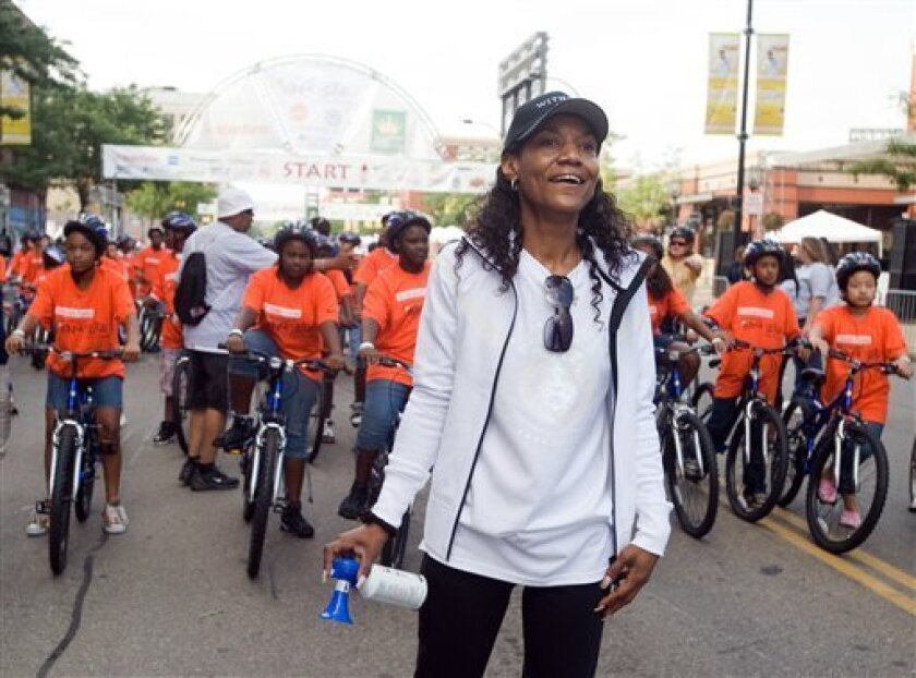 """FILE - This Aug. 22, 2009, file photo shows Gloria James, mother of basketball star LeBron James, watching a group of bike riders as she waits to start another group of riders at the """"King for Kids Bikeathon"""" in Akron, Ohio. Miami Beach police spokeswoman Deborah Doty confirmed that Gloria James was arrested at the Fontainebleau Hotel early Thursday morning, April 7, 2011. She would not say what led to the 4:47 a.m. arrest, or what charges Gloria James may face. (AP Photo/Phil Long, FIle)"""