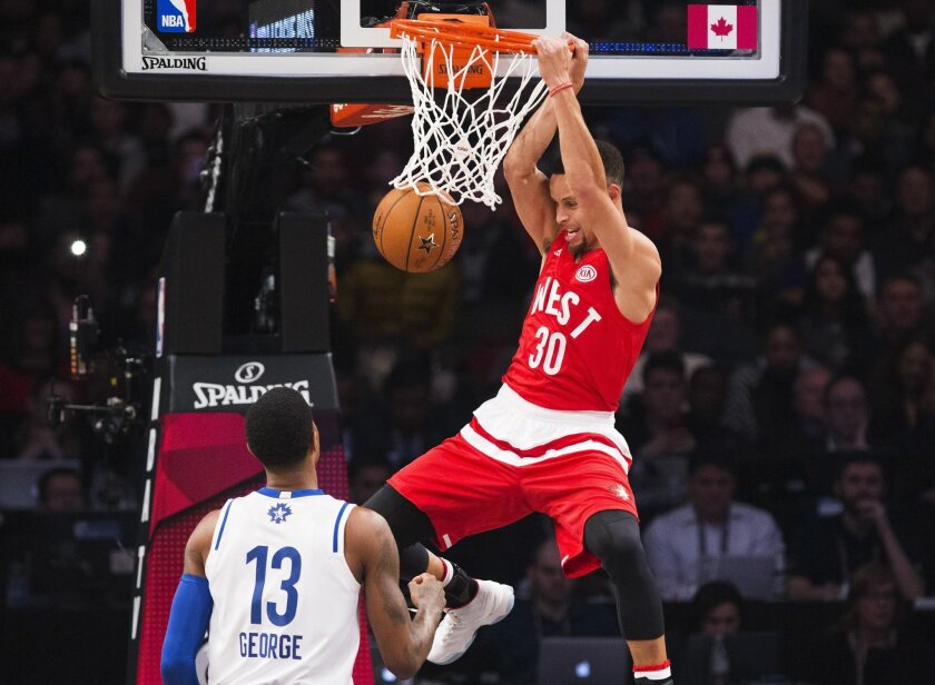 Western Conference's Stephen Curry, of the Golden State Warriors, (30) slam dunks the ball past Eastern Conference's Paul George, of the Indiana Pacers (13) during the first half of the NBA all-star basketball game, Sunday, Feb. 14, 2016 in Toronto. (Mark Blinch/The Canadian Press via AP) MANDATORY