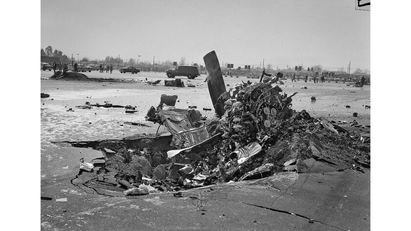 Jan. 31, 1957: An engine from a DC-7B transport is partially buried in the paved surface of school p