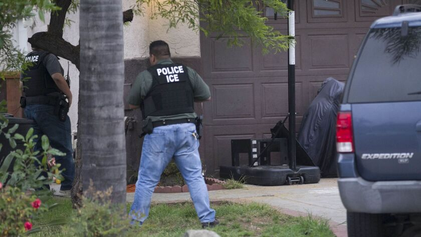 Two officers from ICE's Fugitive Operations team watch the perimeter of a house in Chula Vista in June 2017.