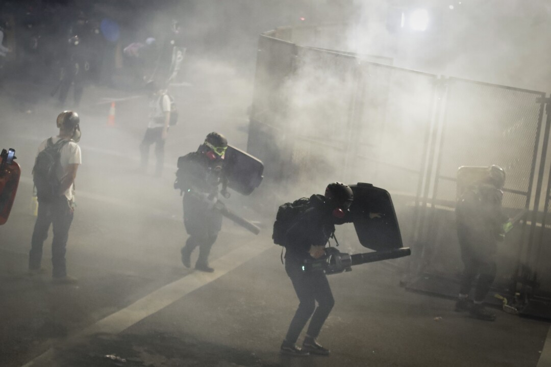Demonstrators use leaf blowers to blow back tear gas launched by federal officers during a protest in Portland, Ore.
