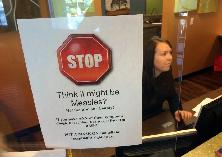 ARCHIVO - En esta fotografía de archivo un letrero advierte de los peligros del sarampión en la recepción del consultorio de un pediatra en Scottsdale, Arizona. (AP Foto/Tom Stathis, archivo)