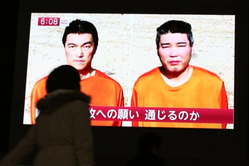 A Tokyo passerby watches a Jan 23 TV news program reporting on two Japanese hostages, Kenji Goto, left, and Haruna Yukawa, held by Islamic State.