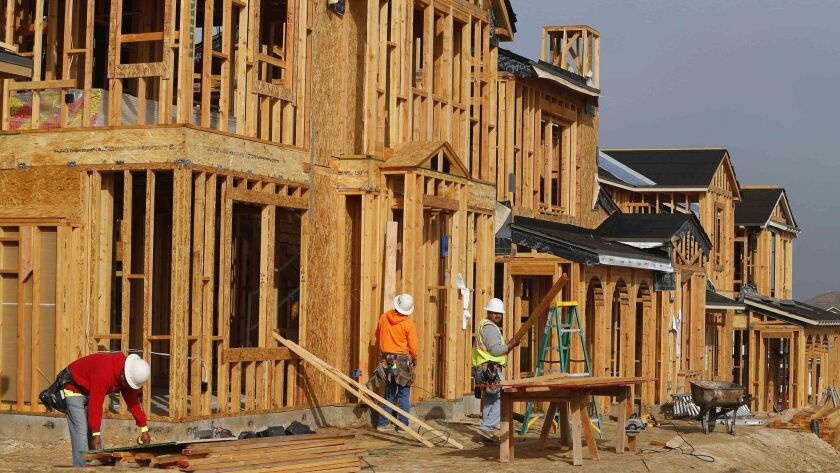 Construction workers build single family homes in San Diego