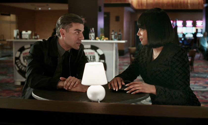 """A man and a woman seated at a table in the movie """"The Card Counter."""""""