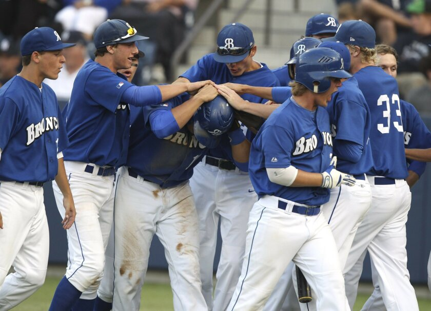 Rancho Bernardo's Alex Jackson is swarmed by teammates after hitting a home run in the San Diego Section Division I championship game.