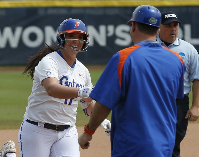 Florida's Lauren Haeger, left, is congratulated by head coach Tim Walton, right, after hitting a home run in the first inning of a game against Tennessee in the NCAA Women's College World Series softball tournament in Oklahoma City, Thursday, May 28, 2015. Florida won 7-2. (AP Photo/Sue Ogrocki)