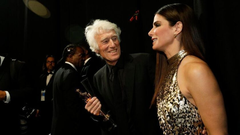 Roger Deakins backstage after winning the cinematography Oscar at the 2018 Academy Awards with presenter Sandra Bullock.
