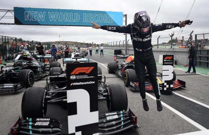 Lewis Hamilton jumps out of his car after his record-breaking 92nd win at the Formula One Portuguese Grand Prix.