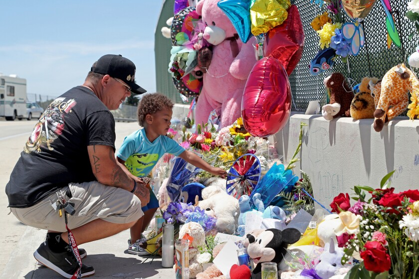 Albert Lamonte looks on as his son Marcel, 2, places a paper pinwheel among a makeshift memorial for 6-year-old Aiden Leos.