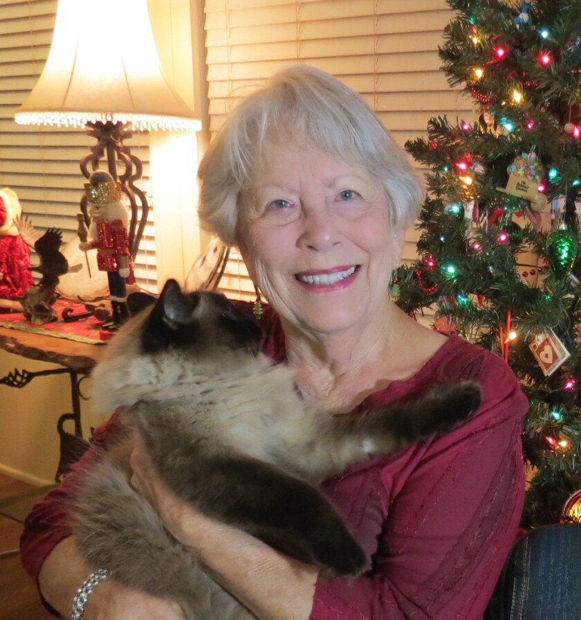Wanda McLaughlin poses with on of her two cats.