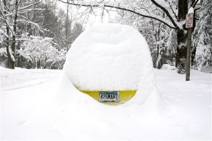 A car with a Minnesota license plate is buried under more than 30 inches of snow during a winter storm in Columbia, Md., Saturday, Feb. 6, 2010. (AP Photo/Carolyn Kaster)