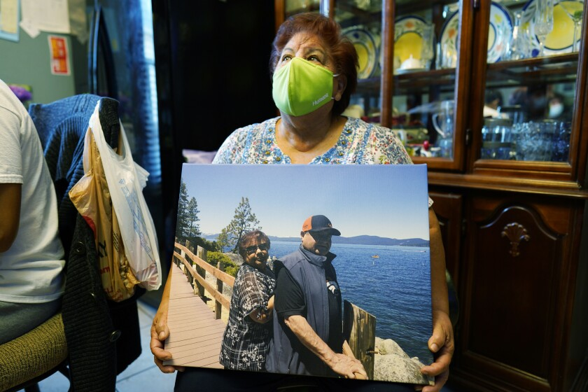 Carolina Sanchez holds a photograph of her husband, Saul, and her taken in 2019 at Lake Tahoe, Nev., during an interview Monday, Oct. 12, 2020, in the family home in Greeley, Colo. (AP Photo/David Zalubowski)