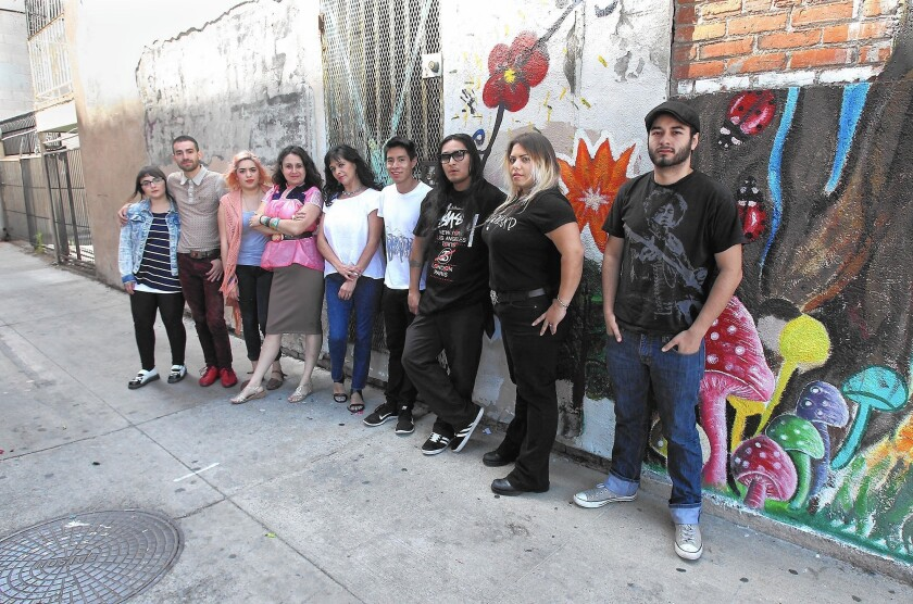 Members of the Santa Ana Community Artist Coalition -- Sabrina Arriaga, Emerson Menjivar, Cynthia Bustos, Alicia Rojas, Victoria Flores, Angel Martinez, Roger Eyes-R, Briyana Negrette and Ricky Cozano -- stand in the alley work space where they hope to start work on a mural reflective of the whole community.