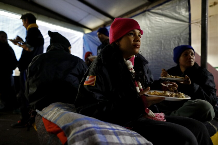 Cuban asylum seeker Jessica Zamora, 18, of Havana, who is pregnant, eats a meal outside Mexico's National Institute of Migration office at the Gateway International Bridge in Matamoros, Tamaulipas state.