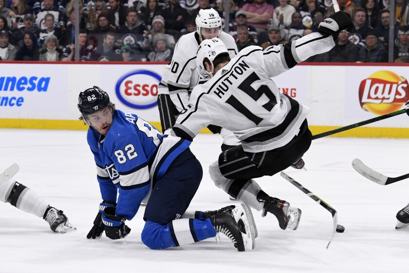 Kings defenseman Ben Hutton (15) falls to the ice while battling with Jets forward Mason Appleton (82) during the second period of a game Feb. 18.