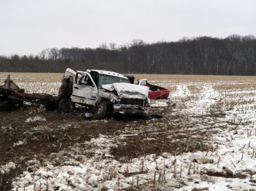 Two pickup trucks are tangled in a field near an intersection where they collided, killing three teens, in Versailles, Ind. The town has been overwhelmed by a string of road accidents that have killed young people.
