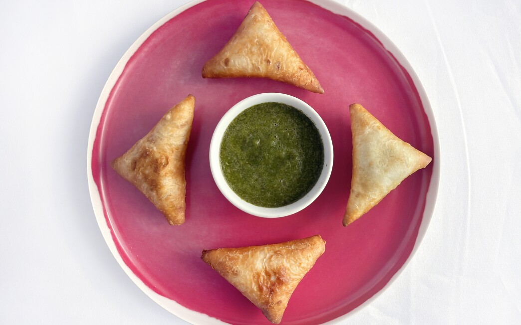 Pacific salmon fills these Somali dumplings, fried until crisp and served with green hot sauce.
