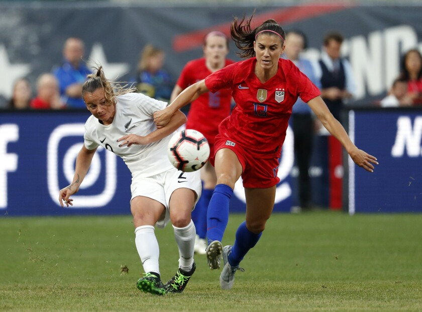New Zealand's Ria Percival, left, and United States' Alex Morgan chase after a loose ball during the