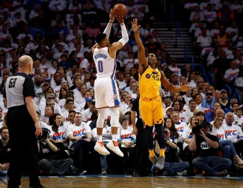 Donovan Mitchell (d) de Utah Jazz intenta bloquear a Russell Westbrook (i) de Oklahoma City Thunder hoy, 18 de abril 2018, durante su juego de la NBA en la primera ronda de los clasificatorios de la Conferencia Oeste en el Chesapeake Energy Arena en Oklahoma City, Oklahoma (EE.UU.). EFE