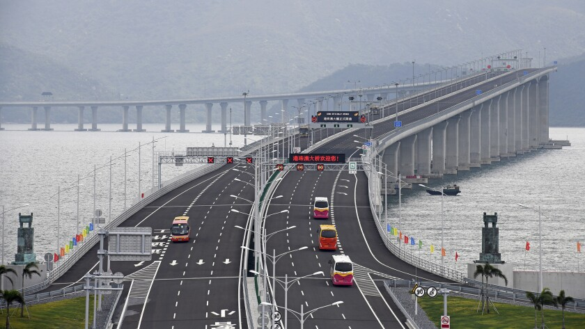 In this photo released by Xinhua News Agency, buses drive on the China-Zhuhai-Macau-Hong Kong Bridge