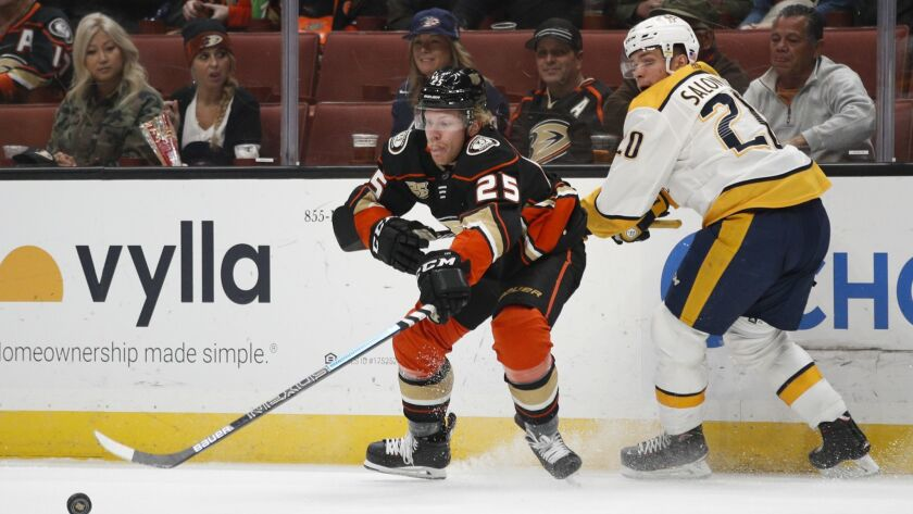 Ducks' Ondrej Kase, center, of the Czech Republic, reaches for the puck against Nashville Predators' Miikka Salomaki, of Finland, during the second period.