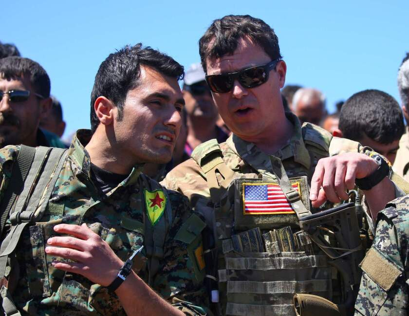 A U.S. officer talks with a fighter from the Kurdish People's Protection Units, or YPG, at the site of Turkish airstrikes in northeastern Syria in April 2017.