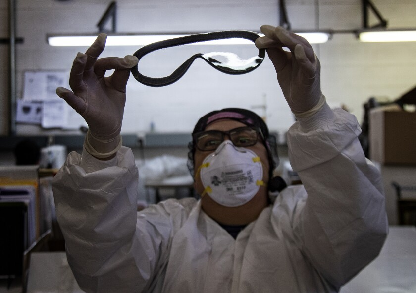 A worker in Temecula, California, in February checks for imperfections on a pair of medical goggles assembled for shipment to China to help prevent the spread of the coronavirus.
