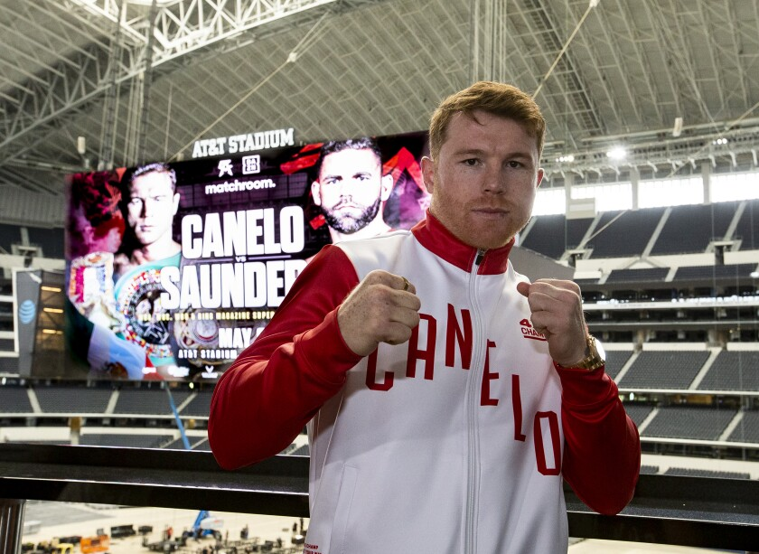 """Saúl """"Canelo"""" Álvarez poses in front a scoreboard promoting his fight with Billy Joe Saunders"""