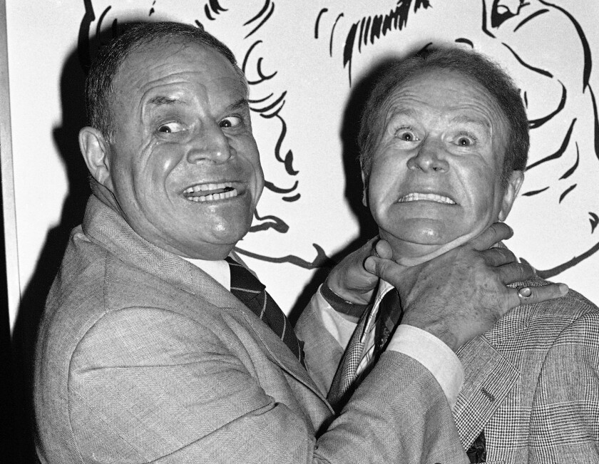 In this Nov. 10, 1977 file photo, Don Rickles pretends to strangle fellow comedian Red Buttons before an annual Stag Roast in Los Angeles.