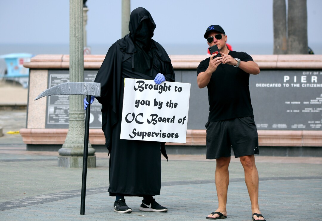Tomas, right, who declined to give his last name, takes a selfie with the Grim Reaper, also known as Spencer Kelly from Huntington Beach, on Friday.