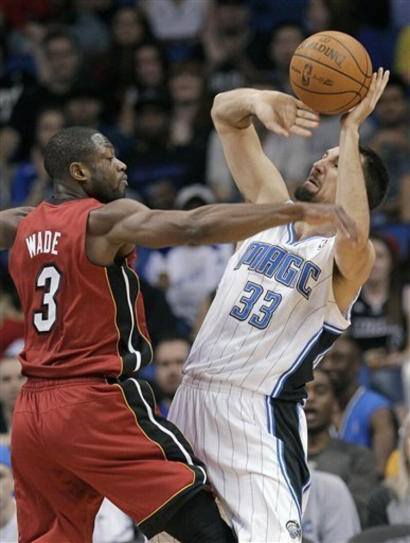 Miami Heat's Dwyane Wade (3) is called for a foul as he knocks the ball out of the hands of Orlando Magic's Ryan Anderson (33) in the first half of an NBA basketball game Wednesday, Feb. 8, 2012, in Orlando, Fla. (AP Photo/John Raoux)