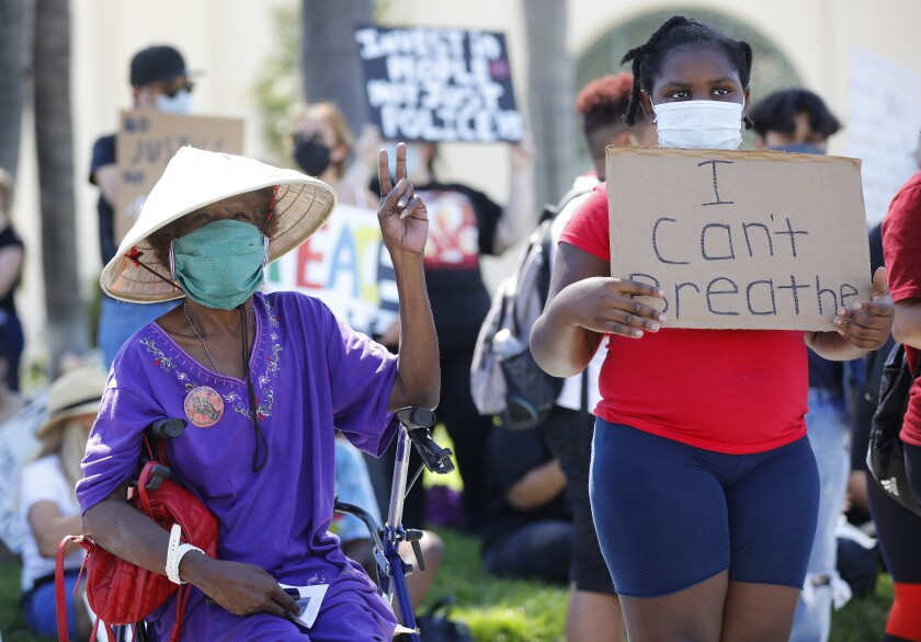 Linda Miles, left, and her great niece Aaniyah Hooker, 9, attend a protest outside Escondido City Hall