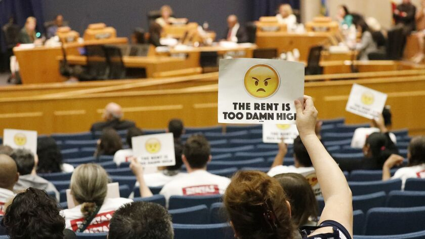 A woman holds up a sign in protest at an April L.A. County Board of Supervisors meeting.