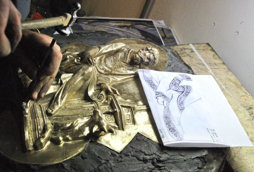 In this photo taken on Monday, July 30, 2012 an artisan hand chisels a panel of the replica of Lorenzo Ghiberti's bronze door, in an atelier in the outskirt of Florence, Italy. A team of artisans on the outskirts of Florence are casting the final panels of a replica of Lorenzo Ghiberti's Renaissance masterpiece, the famed bronze north doors of the octagonal Florence Baptistery, in preparation for its installation in place of the original at the end of January. (Frilli Gallery via AP)