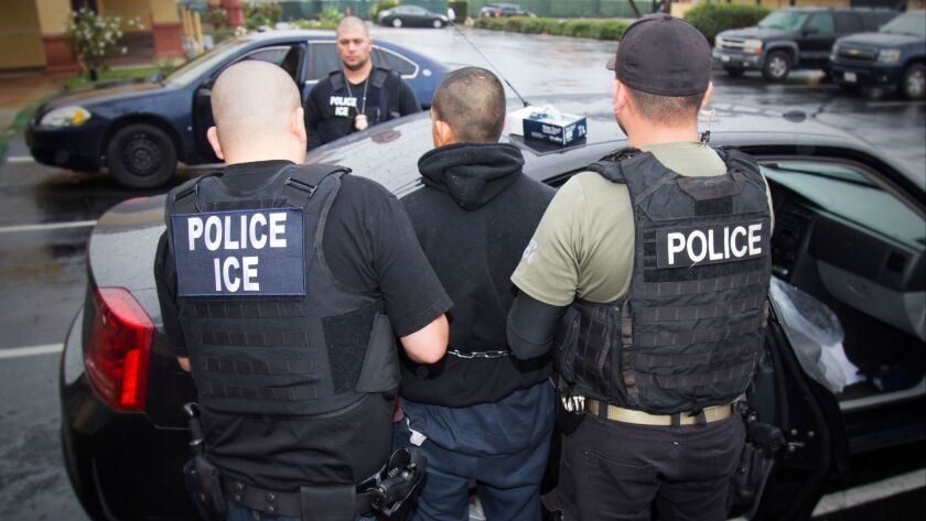 U.S. Immigration and Customs Enforcement agents make an arrest during an operation earlier this month in the Los Angeles area. ICE officials this week told the city of Santa Ana that they were ending their agreement to house immigration detainees at the city's jail.