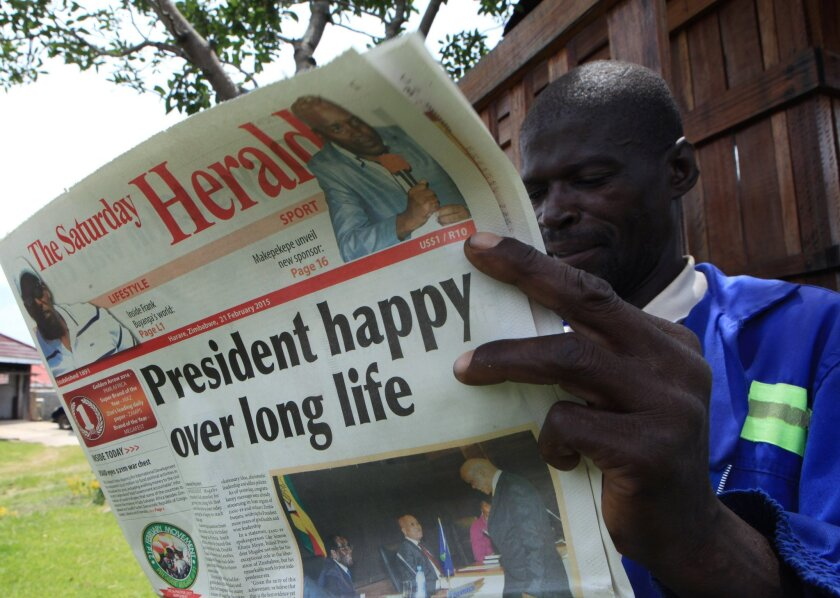 A man reads the state-owned newspaper The Herald in Harare, Zimbabwe's capital, ahead of the Feb. 21 feast marking the 91st birthday of President Robert Mugabe.