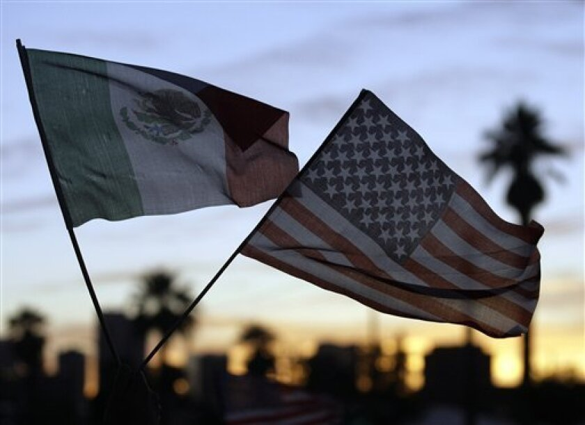 A protester against Arizona's controversial immigration bill waves both the Mexican and U.S. flags  during a march on the State Capitol Wednesday, May 5, 2010, in Phoenix. (AP Photo/Paul Connors)