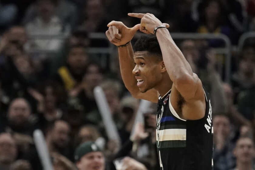 Milwaukee Bucks' Giannis Antetokounmpo appears to place an imaginary crown on his head after hitting his fifth three-pointer Thursday against the Lakers.