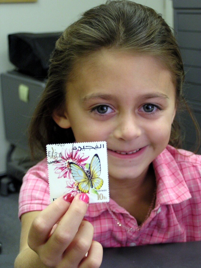 This 2011 photo provided by courtesy of the Postal History Foundation shows a young girl with a stamp participating in the Youth Education thru Stamps Program in Tuscon, Ariz. Stamp collecting rewards patience and persistence, teaching those who embrace it about everything from ancient history to graphic design. And that's exactly why a growing community of parents and teachers believe this retro hobby is worth encouraging today's kids to pursue. (AP Photo/Postal History Foundation, Lisa Dembowski)