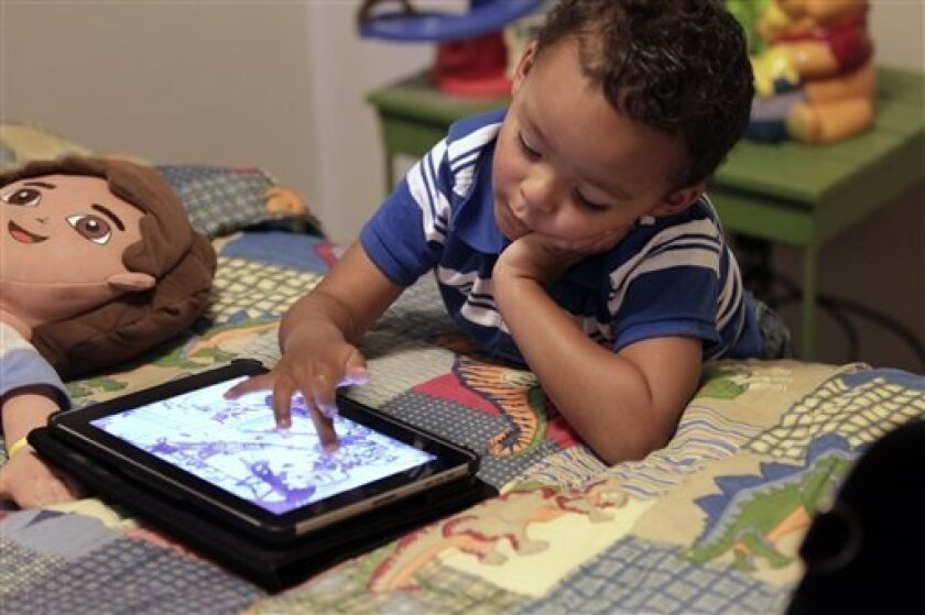 FILE - In this Friday, Oct. 21, 2011 file photo, Frankie Thevenot, 3, plays with an iPad in his bedroom at his home in Metairie, La. As of Wednesday, Aug. 7, 2013, the Campaign for a Commercial-Free Childhood, a Boston-based group, is urging federal investigators to examine the marketing practices of Fisher-Price's and Open Solution's mobile apps. It's the campaign's first complaint against the mobile app industry as part of its broader push to hold accountable businesses that market technology
