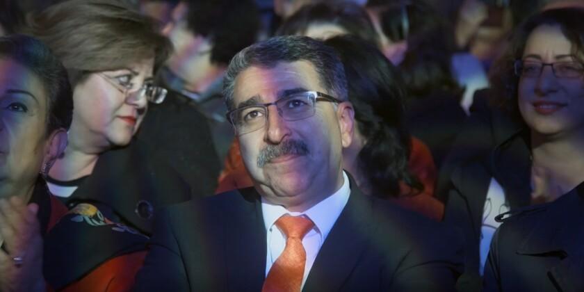 "The mayor of Ramallah, Musa Hadid, seated in audience in the documentary ""Mayor."""